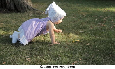 A baby girl crawling on the grass and picking a yellow leaf