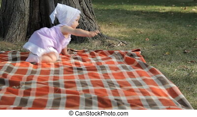 A baby girl crawling over a blanket.