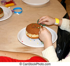 A baby girl decorates a donut. A child is decorating a bun...