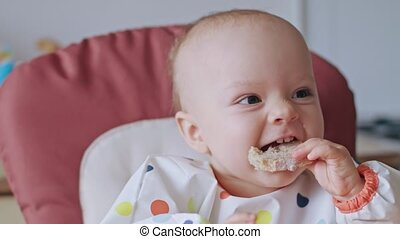 A Baby Girl Eating Bread at Home - A baby girl eating bread...