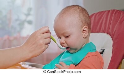 A Baby Girl Eating Puree at Home