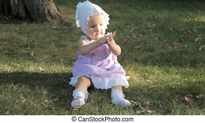 A baby girl in a bonnet sitting on the grass and clapping her hands