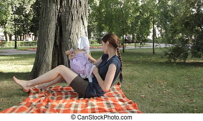 A baby girl in the lap of a young nanny sitting on a blanket spread over grass