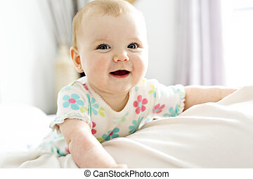 Baby girl in white bedding at home look nice