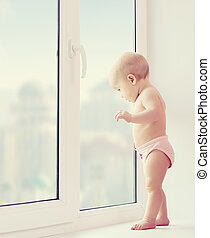 A baby girl looking out the window longing, sadness, and waiting