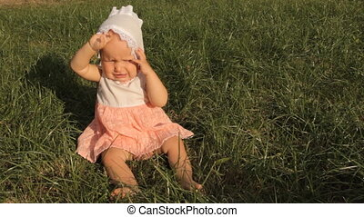 A baby girl rubbing her eyes with hands, the bright setting sun shining right into her face. She starts whining and tears grass around her.