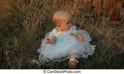 A baby girl sitting in the high grass in a white dress, eating an apricot and looks around. Sunset in summer.