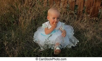 A baby girl sitting in the high grass in a white dress, eating an apricot, smiling and swinging her legs. Sunset in summer.