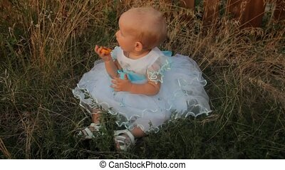 A baby girl sitting in the high grass in a white dress. She gnaws an apricot and looks around. Sunset in summer.