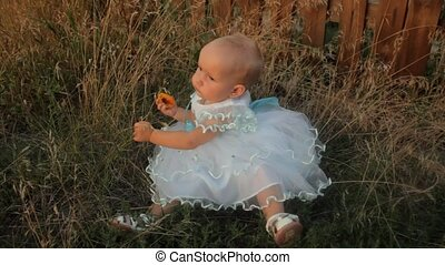 A baby girl sitting in the high grass in a white dress, holding an apricot in her hand. Sunset in summer.