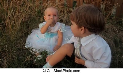 A baby girl sitting in the high grass in a white dress and eating an apricot. A little boy sits near her and puts paper clips in his mouth. Sunset in summer.