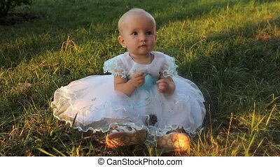 A baby girl sitting on the grass in a white dress and clapping her hands. Sunset in summer.