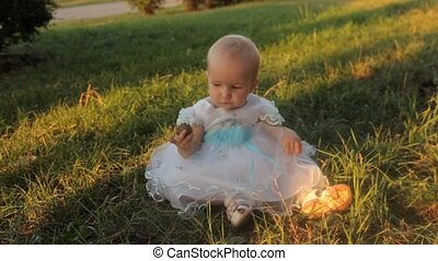 A baby girl sitting on the grass in a white dress, looks at her palm, holding the fir-cone in the other hand. Sunset in summer.