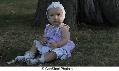 A baby girl sitting on the grass in white socks