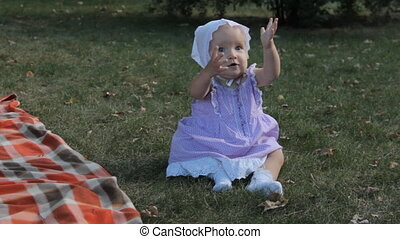 A baby girl sitting on the grass raises her hands