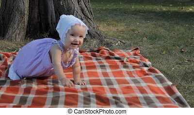 A baby girl smiling and crawling over a blanket