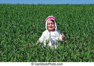 A baby in a green field.