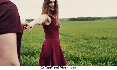 A back view of a happy cuple walking in a field. A beautiful young woman taking her man by the hand.