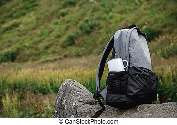 A backpack, a mug, a notepad and a map are lying on the grass. Tourist equipment. The apple lies in the pocket of the backpack. Walk in the forest. Camping in the mountains