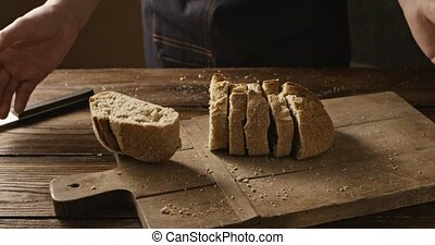 A baker in a black apron throws organic fresh bread on a...