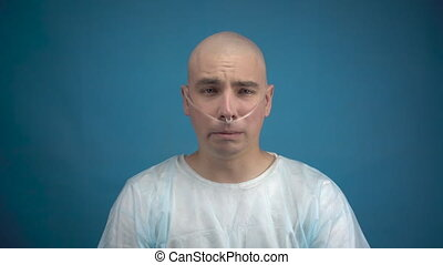 A bald young man with oncology looks at the camera and cries on a blue background. The patient covers his face with his hands. Hair loss due to chemotherapy. 4k