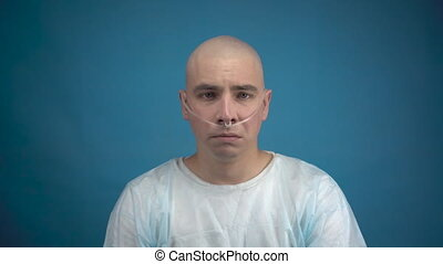 A bald young man with oncology sadly looks at the camera on a blue background. Hair loss due to chemotherapy. 4k