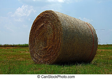A bale of hay in an open field.