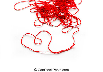 A ball of red wool yarn. Thread laid out the shape of a heart. Closeup. Isolated on white background