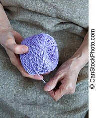 A ball of yarn in the hands of an elderly woman