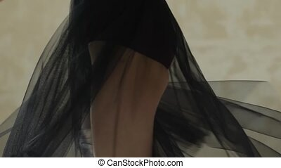 A ballerina in a black translucent skirt is dancing. The ...