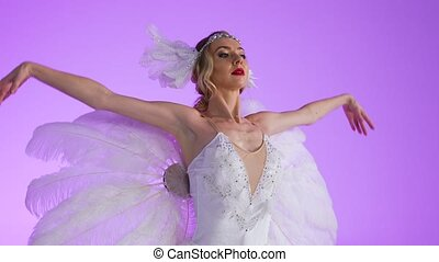 A ballerina in a chic image of a white swan is gracefully dancing on a purple background in a light studio. Festive theatrical dance show, corporate party, birthday. Close up. Slow motion