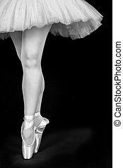 A ballet dancer standing on toes while dancing on black...