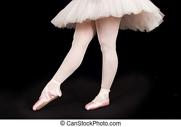 A ballet dancer standing on toes while dancing on black background artistic conversion