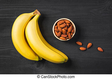 A banch of bananas with almonds on wooden background.