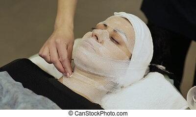 A bandage mask using gauze fabric. Application of cream on...