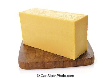 Cheese - A Bar Of Sharp Cheddar Cheese On A Cutting Board