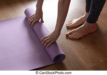 A barefoot woman twists a purple yoga Mat and fitness on the...