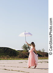 A barefooted girl in a pink dress