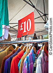 A bargain for a tenner. Second hand clothes rack at market. Portrait orientation.