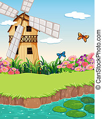 A barnhouse with a windmill near the river