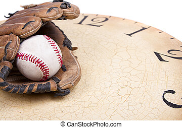 A baseball and mitt on an old vintage clock on an isolated...