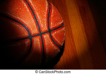 a basketball on the gym floor with dramatic light