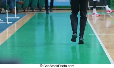A basketball tournament. Players warming up before the...