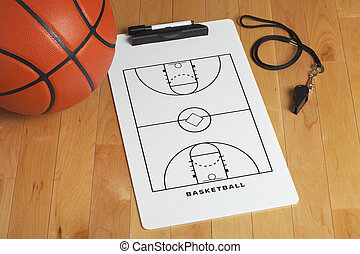 A basketball with coach's clipboard and whistle on a wooden...