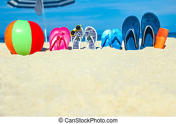 A Beach summer holiday banner background. Flip-flops and hat with a board and ball on the sand near the ocean. Summer accessories on the seashore. Tropical vacation and relax travel concept. Top view and copy space.