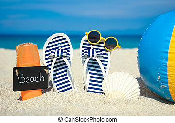 Beach summer holiday banner background. Flip-flops and hat with a board and ball on the sand near the ocean. Summer accessories on the seashore. Tropical vacation and relax travel concept. Top view and copy space.