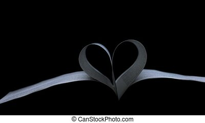 A beam of light slowly glides into the dark studio and illuminates an open book, the pages of which are folded in the shape of a heart, then the light is extinguished. Valentine's day concept. Slow motion. Close up.