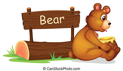 A bear sitting beside a wooden signage
