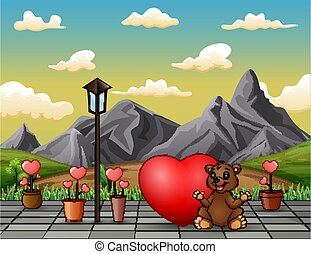 A bear sitting with red heart in the park landscape