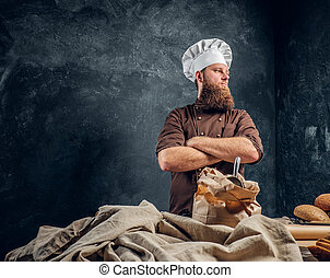 A bearded baker wearing a uniform standing with his arms crossed next to a table, decorated with delicious bread loaves, baguettes and muffins